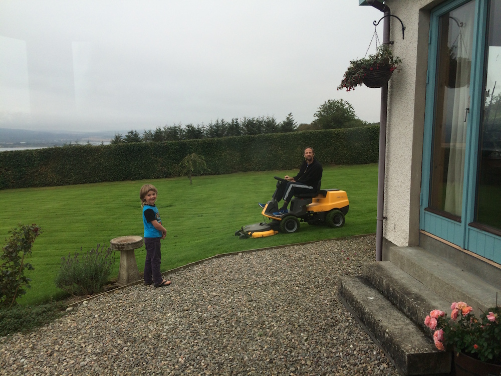 Nathaniel riding the lawn mower at the Scotland housesit