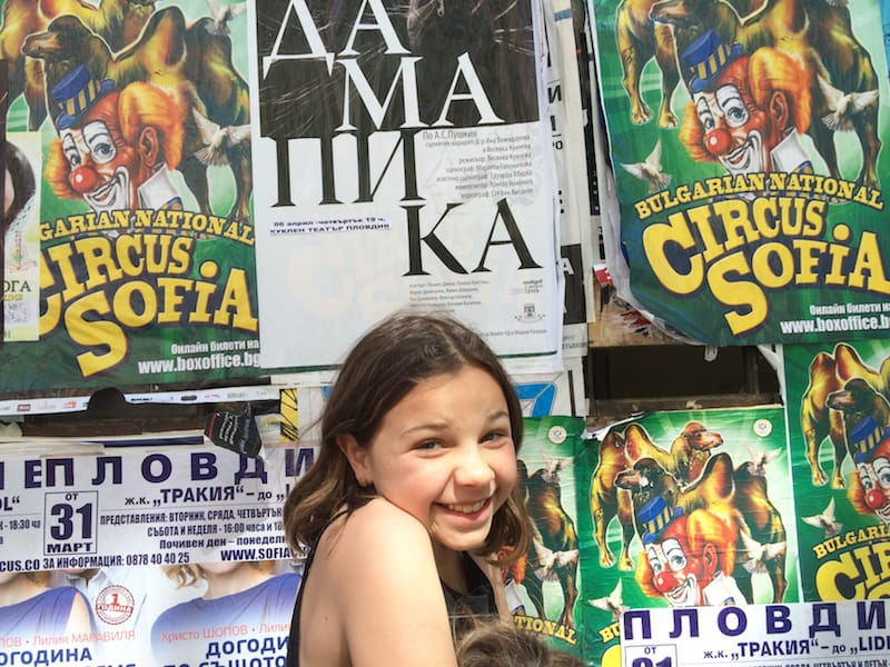 Alpha in front of a bunch of posters on a street in Kapana