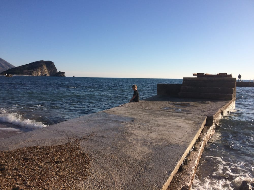 My son sitting on the pier at Budva Beach